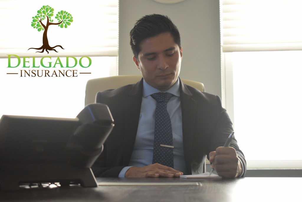 Manny in the office with Delgado Logo 1024x683 - Delgado Insurance-Protecting you with Business Insurance